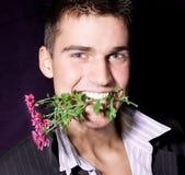 强壮男子的人在嘴拿着一朵花 库存图片