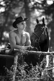 强壮男子的人英俊的牛仔和马 免版税库存照片