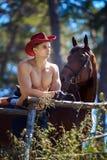 强壮男子的人英俊的牛仔和马 库存图片