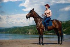 强壮男子的在一匹马的人英俊的牛仔骑马在天空和水背景  免版税库存照片