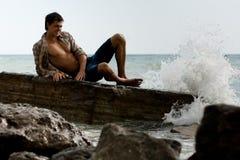 强壮的小伙子海运石头 免版税库存照片