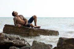 强壮的小伙子海运石头 免版税库存图片