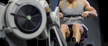 强有力的可爱的肌肉人CrossFit教练员做在室内划船者的锻炼在健身房 免版税库存照片