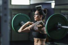 强有力的可爱的肌肉妇女CrossFit教练员做与杠铃的锻炼 库存图片