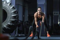 强有力的可爱的肌肉CrossFit教练员作战与绳索的锻炼 免版税库存照片