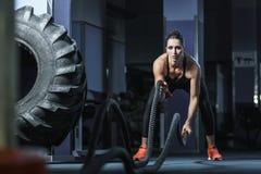 强有力的可爱的肌肉CrossFit教练员作战与绳索的锻炼 库存图片