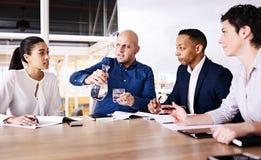 强有力的少妇谈话与三个同事的注意 免版税图库摄影