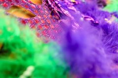 强烈的颜色-在紫色和绿色的Mardi Gras - Carnaval背景-被弄脏的羽毛和一个面具在金背景 库存照片