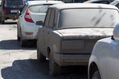 强烈肮脏的汽车在城市街道上停放了 库存图片