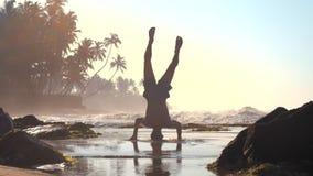 强的体操运动员剪影在湿沙子的头平衡 影视素材