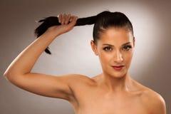 强的健康头发-妇女拿着在灰色背景的马尾 免版税库存照片