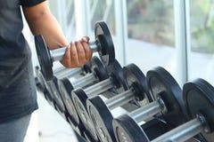 强的妇女手采取在健身房的一个重的哑铃 图库摄影