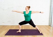 强的妇女训练瑜伽在健康生活方式概念的现代演播室家 免版税库存图片