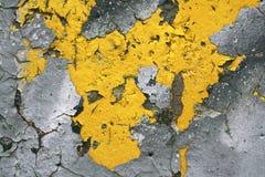 强的表面结构以其余在混凝土墙上的黄色油漆抽象背景的 库存照片