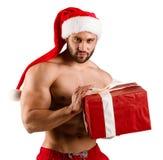 强的躯干和佩带在有muschular身体和大礼物盒的圣诞老人帽子的曲线白人,被隔绝 图库摄影