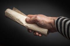 强的水手手拿着滚动的老被弄皱的纸 免版税库存照片