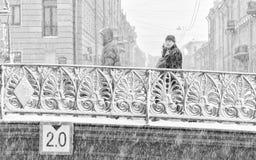 强的暴风雪在圣彼得堡 走沿Demidov桥梁的人们 库存图片