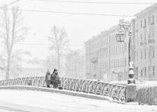 强的暴风雪在圣彼得堡 走沿Demidov桥梁的人们 免版税库存图片
