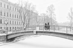 强的暴风雪在圣彼得堡 走沿Sennoy桥梁的人们 免版税库存照片