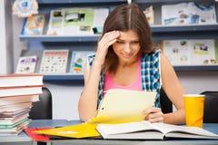 强调的女学生在图书馆里 免版税图库摄影