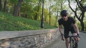 强运动骑自行车者冲刺艰难在马鞍外面 穿黑运动服的自行车车手登高的小山 t 股票录像
