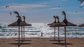 强风、背后照明和秸杆遮阳伞的风筝冲浪者在海滩。 免版税库存照片