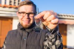 归属、不动产、物产和房客概念-一把快乐的年轻人藏品钥匙的画象从新的家的 免版税库存照片