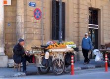 当一个人走过去,卖从一个摊位的一个人果子在推车坐路面在街角的尼科西亚塞浦路斯 库存图片