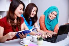 当一起时,学习三位大学生看起来愉快 免版税库存照片