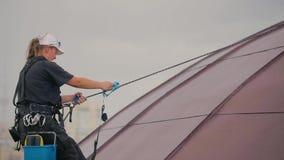 当下雨时,妇女登山人上升在圆顶屋顶 股票视频