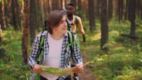 当不同种族的小组朋友是时,微笑的年轻人看地图并且搜寻正确的方式在森林里