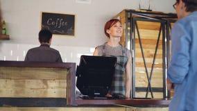 当买咖啡对去在咖啡馆早晨时,愉快的人民支付与手机 食物和饮料服务 股票录像