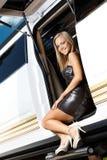 当事人成套装备的性感的女孩在大型高级轿车门 免版税图库摄影