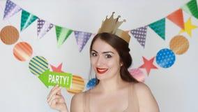 当事人 愉快的生日 滑稽的女孩微笑 庆祝的装饰 一名年轻愉快的妇女的画象金黄冠的 股票视频