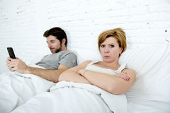 当互联网上瘾者丈夫使用手机社交networ时,在床不满意的妻子的年轻夫妇使沮丧和恼怒不耐烦 库存照片