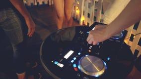 当人们在获得附近跳舞乐趣时, DJ ` s手调整在创造音乐的混合的控制台的声音 专业人员 影视素材