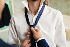 当他们在屋子里时,站立新郎` s朋友帮助修理在新郎` s脖子的一条蓝色领带 免版税库存照片