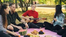 当他们的朋友俏丽的女孩弹在野餐的吉他时,激动的女孩和人是唱和拍手 股票视频