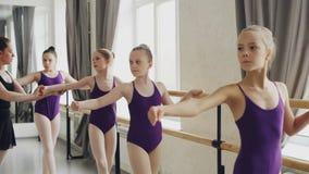 当他们的老师帮助他们时,逗人喜爱的小女孩有做锻炼的芭蕾舞蹈艺术类在芭蕾酒吧 影视素材