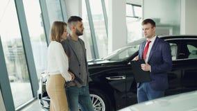 当他告诉他们关于豪华汽车时,感兴趣的夫妇男人和妇女与经理在售车行中谈话 影视素材