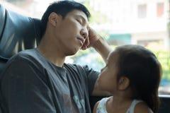 当他在公共汽车时,睡觉女孩看她疲乏的爸爸 免版税图库摄影