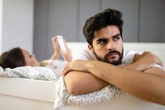 当他的互联网上瘾者妻子在人脉时,使用手机丈夫沮丧,弄翻了 免版税库存图片