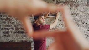 当他的妻子做与她的手指时的框架形状快乐的人选择现代图片的地方砖墙的 影视素材