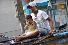 当他通过与他的一艘竹木筏的父亲在曼谷,一条被充斥的街道一个小男孩打手势一wai给摄影师, 免版税库存图片