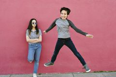 当他青少年的姐妹观看无印记精力充沛时,年轻男孩跳高 库存图片