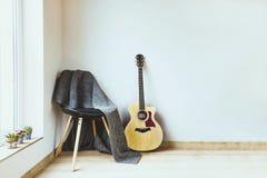 当代家庭内部 用羊毛灰色毯子和声学吉他盖的黑椅子在空的白色墙壁前面 库存照片