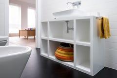 当代白色被绘的MDF卫生间单位,与五颜六色的篮子和黑乙烯基地板 免版税库存照片