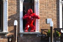 当代艺术:站立在窗口里的一只红色猴子的雕塑 库存图片