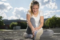 当做炫耀时,运动服的一个少妇她的脚腕受伤 库存照片