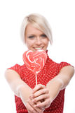 当前一个红色心形的棒棒糖的妇女 免版税图库摄影